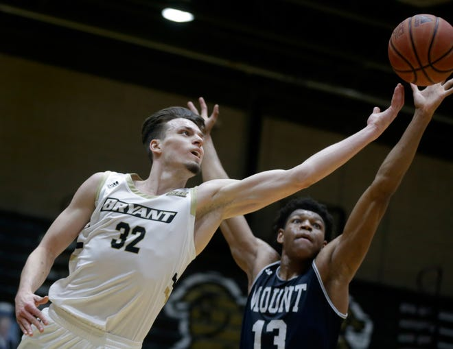 Bryant's Peter Kiss, who finished with 12 points before fouling out, leans into a layup to get past Mount defender Mezie Offurum in the first half of Tuesday night's NEC championship game.