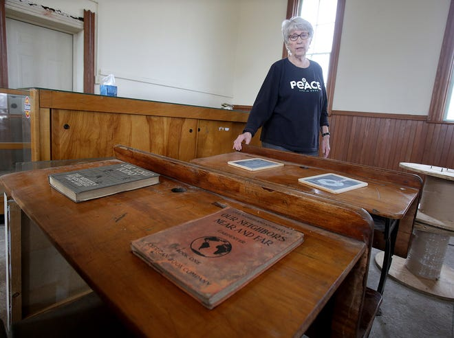 Sue Johnston, spokeswoman for the Perry History Club, talks about desks from the era of the Genoa one-room schoolhouse that will be used when the building is completely refurbished.