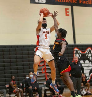 Harlem's Lathan Lewis leaves his feet to make a pass against Jefferson on Tuesday at Harlem High School in Machesney Park.