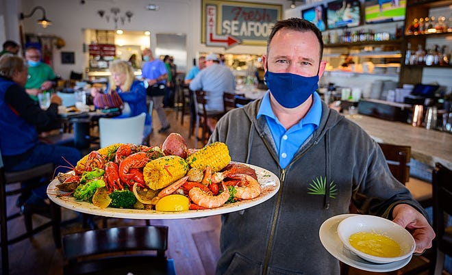 Chad Heiland, a manager at St. Augustine Fish Camp, holds a low-country boil tray in the restaurant's dining room on Friday, March 5, 2021.