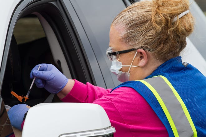 An Atrium Health employee administers a COVID-19 vaccine Saturday outside of Shelby High School.