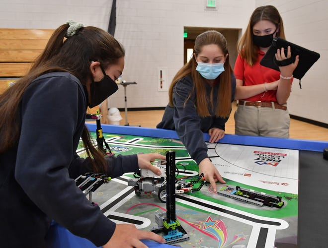 Seventh-grade students at St. Martha Catholic School, from left, Ana Martinez, Keira Smith and Ainsley Young, program a robot to follow a path and perform tasks Wednesday morning during a demonstration at the school.