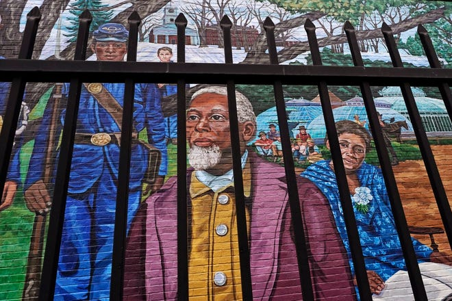 Past Amherst, Mass., area residents Henry Jackson, center, Lt. Frazar Stearns, left, and Anna Reed Goodwin, right, are featured on the Amherst Community History Mural, as seen through the adjacent West Cemetery fence, Friday, Jan. 15, 2021, in Amherst, Mass. Amherst is on a path toward providing reparations to Black residents for past injustices following the town council's adoption of a resolution calling for the community to become an anti-racist town.