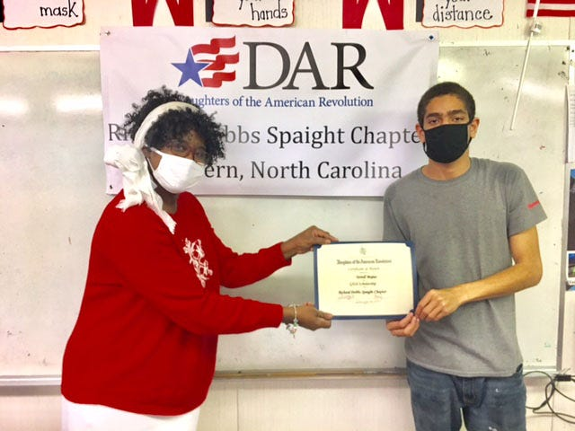 Terrell Mejias, an adult student with the Craven County Family Literacy Program in Vanceboro, was recently awarded a G.E.D. Scholarship from the Richard Dobbs Spaight Chapter of the Daughters of the American Revolution. The award was presented by Regina Edmonds, a teacher for adults enrolled in the Family Literacy site at Vanceboro Farm Life School.  Terrell, who also works for a local business, was originally referred to the program by the Vanceboro Christian Help Center, where he regularly volunteers. The Richard Dobbs Spaight Chapter, NSDAR works to promote literacy in the community in various ways, including partnering with other literacy-focused organizations.  For the past three years, the Literacy Promotion Committee has awarded a scholarship to an adult student who is working to earn their High School Equivalency (HSE) Diploma through the Family Literacy Program, in collaboration with Craven Smart Start. The scholarship was created to assist a deserving student with the cost of the four tests they must take to earn their HSE Diploma. DAR members are involved in a variety of service projects promoting historic preservation, education and patriotism. For more information on the Richard Dobbs Spaight Chapter, NSDAR, please contact DARRichardDobbsSpaight@gmail.com