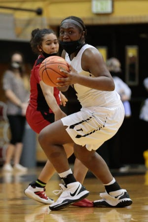 Topeka High junior NiJaree Canady steals the ball from Wichita Heights in the second quarter of Tuesday's game. The Trojans won 71-36.