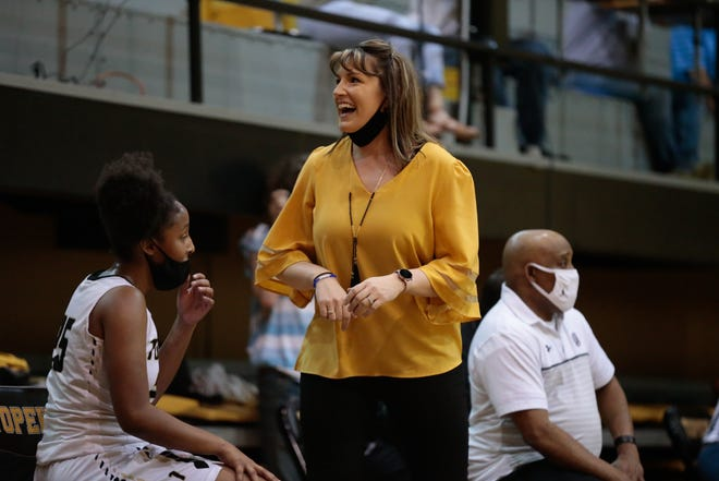 Topeka High coach Hannah Alexander smiles to fans after the Trojans pull further ahead of Wichita Heights during Tuesday's game. The Trojans won 71-36.