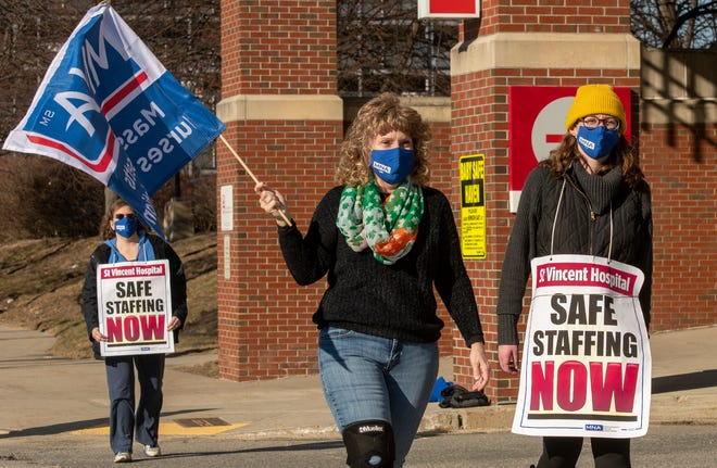 Nurses Denise Scotia, center, and her daughter Betsy Scotia, right, walk the picket line outside the emergency department entrance to St. Vincent Hospital, March 9, 2021.