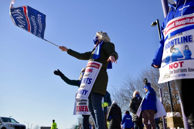 St. Vincent Hospital nurse Karin Rock waves a flag on the pick line Wednesday morning. The strike at the hospital entered its third day.