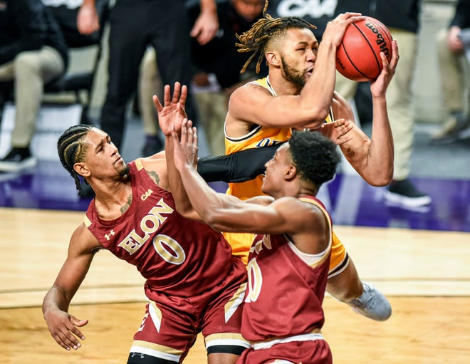 Drexel's Tim Perry Jr. tangles with Elon's Hunter McIntosh, left, and Kris Wooten, front, during the CAA Tournament championship game Tuesday night.