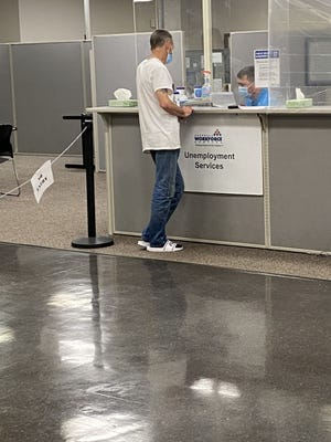 A man stands in line at the Unemployment Office in Fort Smith.