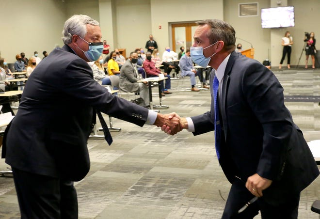 Bryan Kindred, president and CEO of DCH Health System shakes hands with Mike Daria, superintendent of Tuscaloosa City Schools, after Daria presented the first Achiever's Coin to the DCH System in appreciation of their service to teachers Tuesday, March 9, 2021. [Staff Photo/Gary Cosby Jr.]