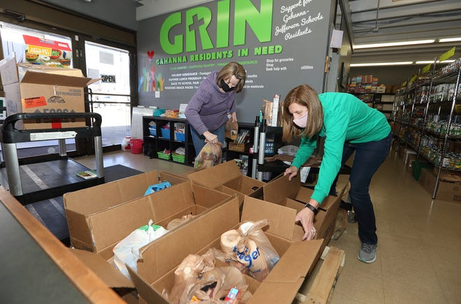 Donna Trotter (left) and Kathy O'Hara, both of Gahanna and volunteers at Gahanna Residents In Need, put items into a food box March 5 to be delivered to clients as part of GRIN's new mobile-unit delivery program.