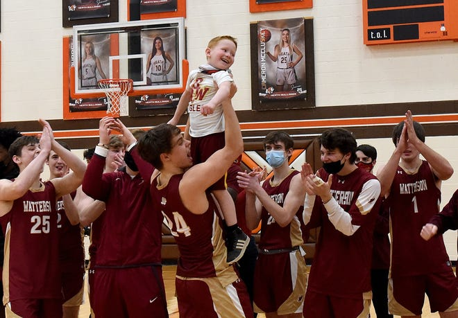 Watterson's Jake Hoying lifts Blake Devlin, son of assistant coach Steve Devlin, while the Eagles celebrate a 44-35 victory over host Heath in a Division II district final March 6. It was Watterson's first district title since 2014.