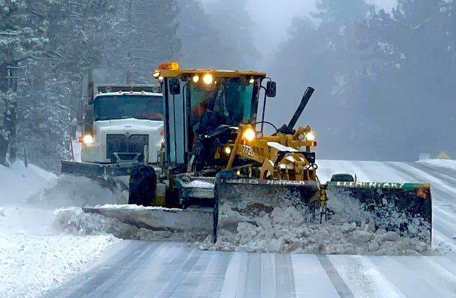A Caltrans crew plows snow in the mountain community of Fawnskin, near Big Bear. A winter storm on Wednesday, March 10, 2021, brought rain to the High Desert and snow to the local mountains.