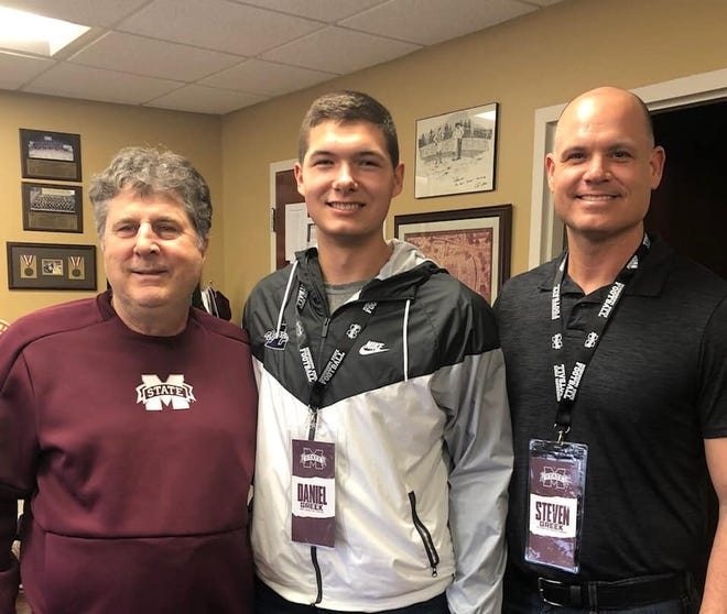 Coach Steven Greek (right) and his oldest son Daniel, a freshman quarterback at Mississippi State, visit with MSU head coach Mike Leach (left). Greek was hired on Tuesday night as the new head football coach and athletic director at Ferris High School.
