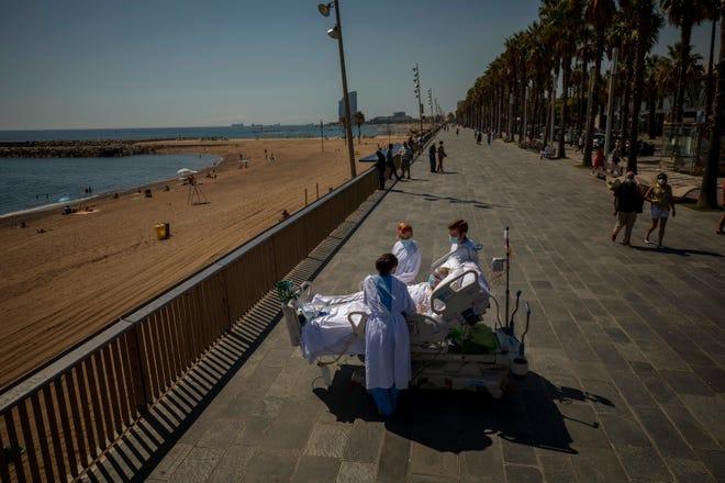 """FILE - Dalam file foto 4 September 2020 ini, Francisco Espana, 60, dikelilingi oleh anggota tim medisnya saat dia melihat ke laut Mediterania pada 4 September 2020, dari tempat berjalan-jalan di sebelah """"Rumah Sakit del Mar."""" di Barcelona, Spanyol. Francisco menghabiskan 52 hari di unit Perawatan Intensif di rumah sakit karena virus korona, tetapi hari ini dia diizinkan oleh dokternya untuk menghabiskan hampir sepuluh menit di pantai sebagai bagian dari terapi pemulihannya."""