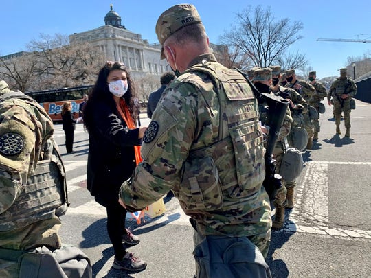 Rep. Rashida Tlaib, D-Detroit, hands a letter to members of the Michigan National Guard during a lunch break on Wednesday, March 10, 2021.