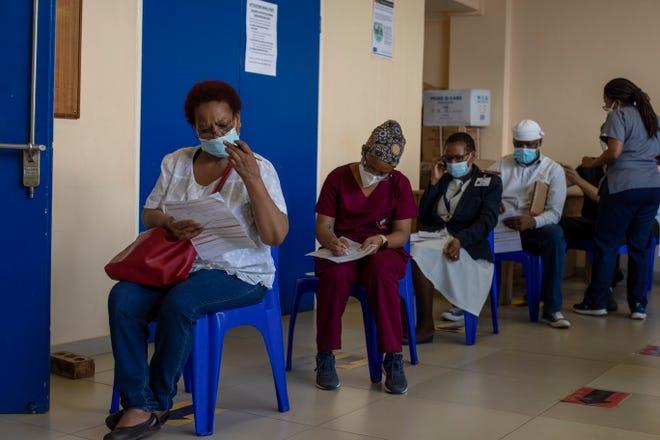 Maggie Sedidi, kiri, perawat berusia 59 tahun di rumah sakit Chris Hani Baragwanath di Soweto, membaca pertanyaan medis sebelum menerima dosis vaksin Johnson & Johnson COVID-19 di pusat vaksinasi di Soweto, Afrika Selatan, Jumat, 5 Maret , 2021.