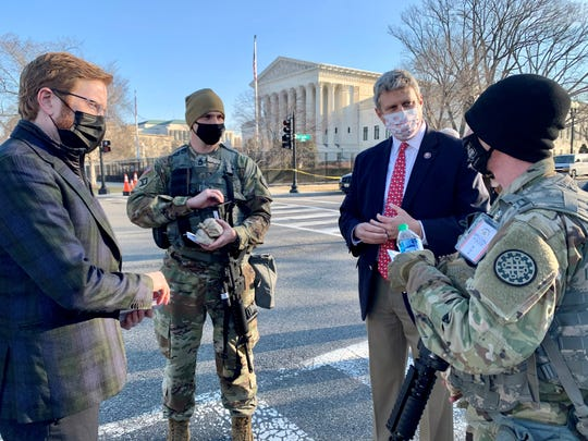 U.S. Rep. Peter Meijer, at left, and Rep. Bill Huizenga chat with members of the Michigan National Guard during a food drop across from the U.S. Capitol on Wednesday, March 10, 2021.