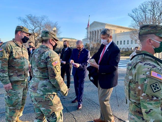 Perwakilan AS Bill Huizenga, Tim Walberg, dan Peter Meijer membagikan sandwich sarapan dan kartu hadiah kepada anggota Pengawal Nasional Michigan di seberang jalan dari Gedung Kongres AS pada hari Rabu, 10 Maret 2021.