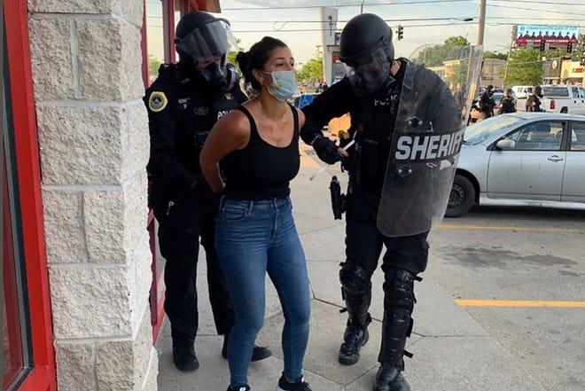 Petugas polisi terlihat menangkap reporter Des Moines Register Andrea Sahouri setelah protes Black Lives Matter yang dia liput pada 31 Mei 2020, di Des Moines, Iowa, dibubarkan oleh gas air mata.