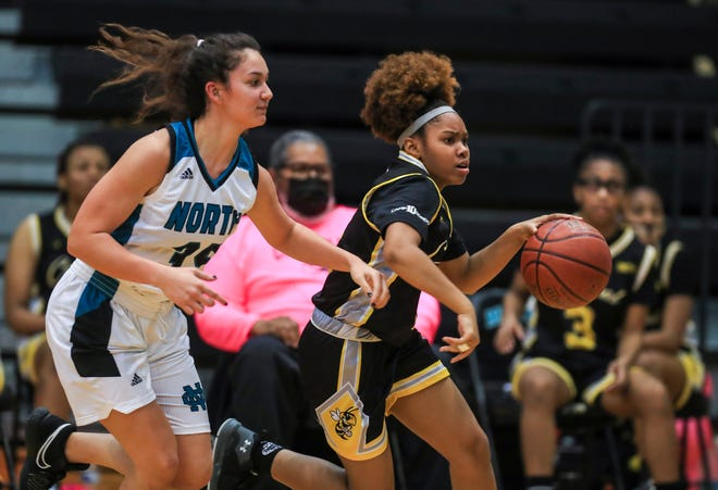 Central's JaKyrra Bartlett drives by North Oldham's Alaina Leber at North Oldham High School Tuesday night. March 6, 2021