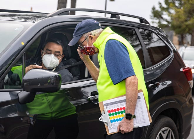 Bill Miles,76, verifies drivers appointments before they are given their COVID-19 vaccine at the Germantown Baptist site on Wednesday, March 10, 2021.