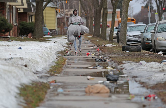 Cashimier Wright of Milwaukee carries a stuffed animal for his girlfriend as he walks along a litter-covered sidewalk along West Locust near North 13th Street in Milwaukee on Wednesday, March 10, 2021.