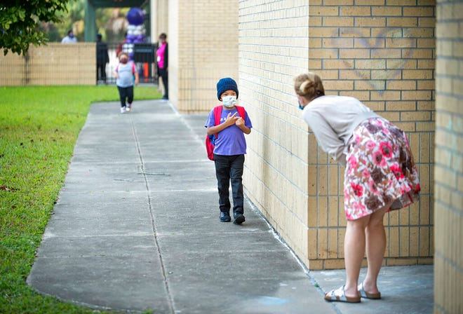 First grade teacher Bella Legault bends down to greet a nervous incoming student on the first day back at school for fifth-12th grade students at Foundation Preparatory School in New Orleans on Monday, Oct. 12, 2020.
