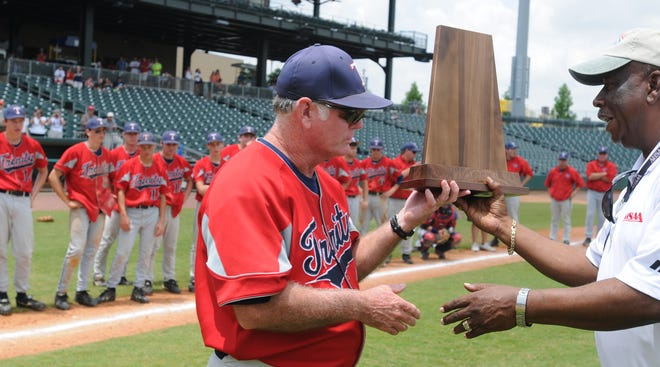 Trinity Presbyterian baseball coach Ken Whittle accepts the AHSAA 3A 2nd place trophy from Joe Evans, AHSAA Associate Executive Director, following their game with Madison Academy at Riverwalk Stadium in Montgomery, Ala. on Friday, May 15, 2009.