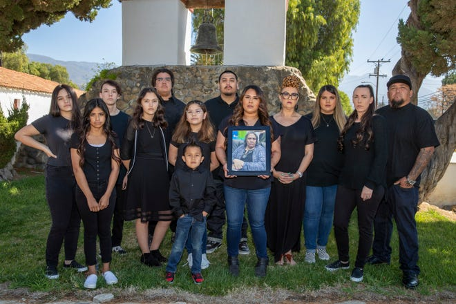 April Cantu, center, holds a photograph of her late mother, Jo Ann Smith, while flanked by family outside the Mission San Antonio De Pala in Pala, Calif., on March 6, 2021. Smith, a member of the Pala Band of Mission Indians, died of COVID-19.