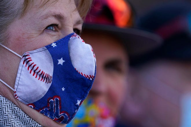 Fans wear face masks as they watch a spring training baseball game between the Kansas City Royals and the Texas Rangers on Feb. 28, 2021, in Surprise.