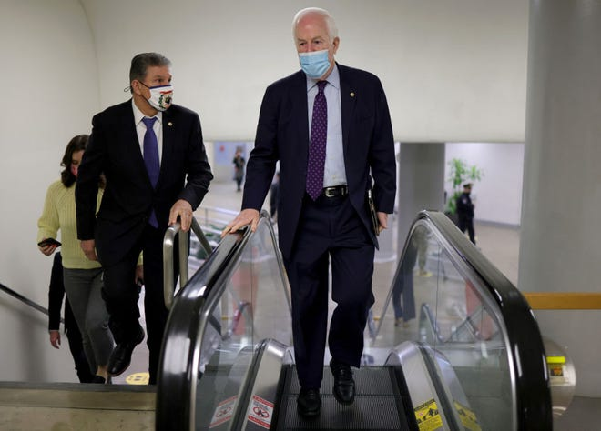 Sen. John Cornyn, R-Texas, right, talks with Sen. Joe Manchin, D-W.Va., while walking to the U.S. Senate chamber for a vote on March 5, 2021, in Washington, D.C. The Senate approved the latest COVID-19 relief bill early Saturday morning. (Win McNamee/Getty Images/TNS)