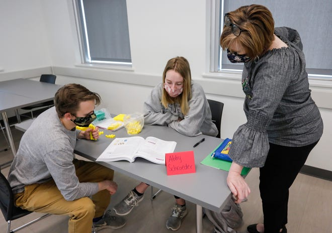 Stefanie Livers, right, works with her students Matthew Herber, left, and Abby Schroeder on base ten blocks which are used to teach children math during the Elementary Math Methods course at Missouri State University on Wednesday, March 10, 2021.