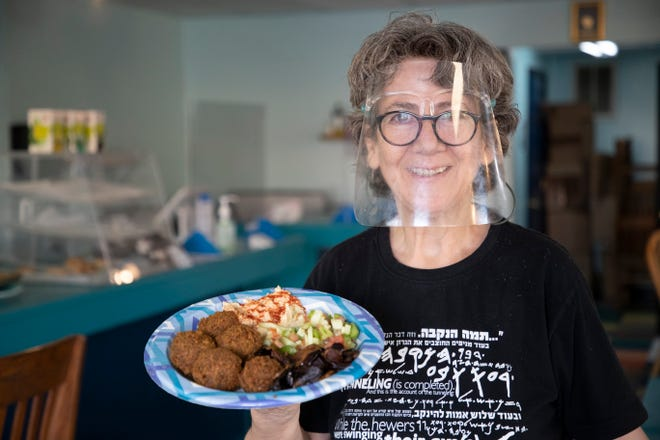 Cafe Yerushalmi Owner Magi Mekaiess holds a plate of falafel and sides at her restaurant on Lake Bradford Road Tuesday, March 9, 2021.