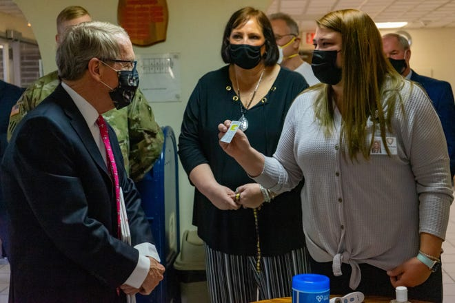 Ohio Gov. Mike DeWine gets a close up view of the vaccination cards reminding recipients to return for their second dose of the Moderna vaccine.  He stopped by a vaccination clinic at Maple Terrace High Rise Apartments Wednesday, in an effort to reach senior populations that might have limited access to clinics due to personal limitations.