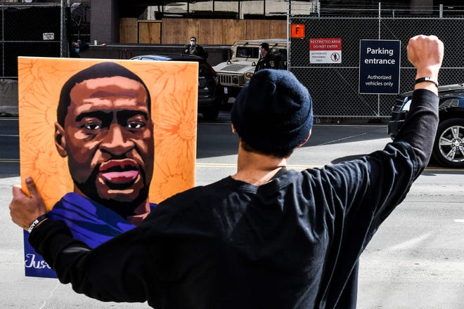 An demonstrator holds a portrait of George Floyd outside the Hennepin County Government Center on March 9, 2021 in Minneapolis.
