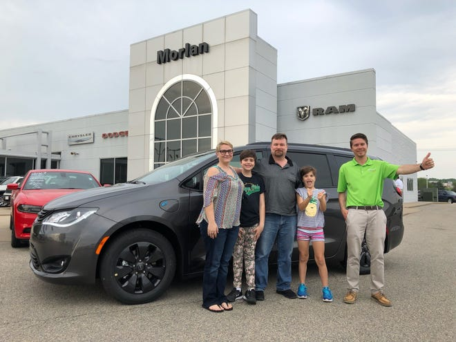 The Salina, Kansas, family of (l-r) Sarah Spurlock, Juliahna Brown, Joel Spurlock and Jillian Brown pose with sales person Wes Adelman in front of the Chrysler Pacifica plug-in hybrid electric vehicle they bought from Morlan Chrysler Dodge Jeep Ram in Cape Girardeau, Missouri.