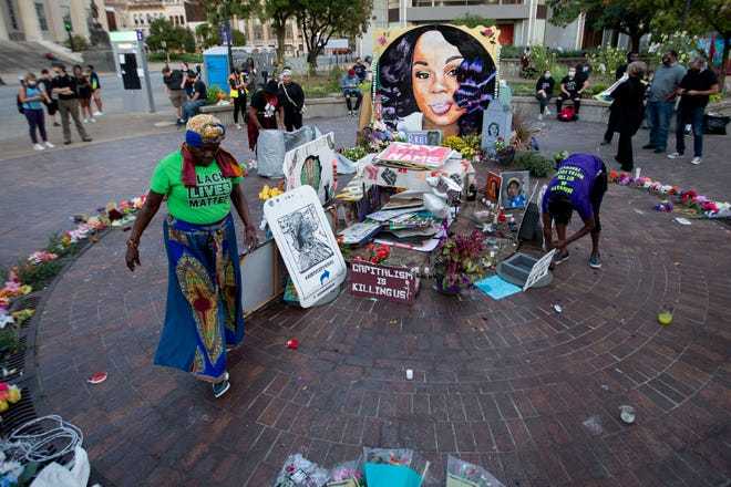 Earline K. (left) and Rosie Henderson work to collect and cover the Breonna Taylor memorial with a tarp to protect it from rain Sept. 27, 2020, in downtown Louisville, Ky.