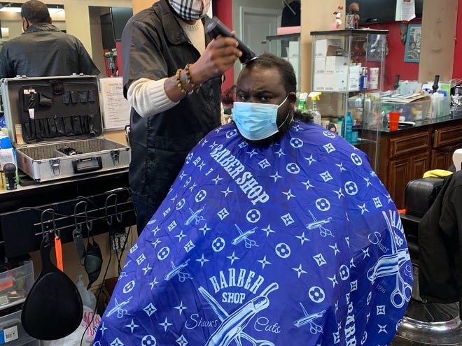 Mike Brown, who runs a barber shop in a strip mall in Hyattsville, Maryland, has been combating conspiracy theories about the COVID vaccines spreading on social media like Facebook, Instagram, Twitter and YouTube.