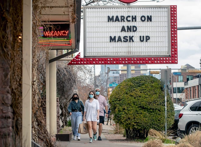 Juan Tenorio and his daughters, Abagail, 20, and Isabel, 18, walk past a sign encouraging masking in Austin on Tuesday, a day before the end of a statewide mask mandate.