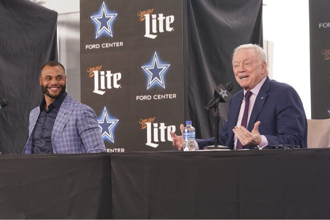 Dallas Cowboys quarterback Dak Prescott, left, looks on and smiles as team owner Jerry Jones speaks during a March press conference announcing Prescott's new contract with the team. The Cowboys will pay Prescott $160 million over four years.