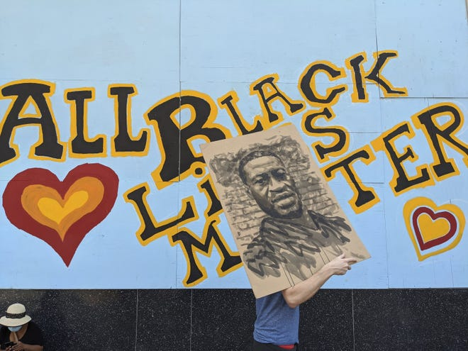 "A demonstrator carries an image of George Floyd in front of a mural reading ""All Black Lives Matter"" during a march in  Los Angeles in February. [AP Photo/Damian Dovarganes, File]"