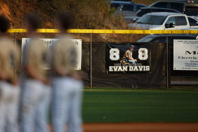 A banner honors Evan Davis while teammates stand for the National Anthem on Tuesday, March 9, 2021 at American Veterans Memorial Park in Commerce. The Commerce Tigers are wearing number 8 on the back of their hats in honor of Davis, who died in a car crash on July 15, 2020. (Julian Alexander for the Athens Banner-Herald)