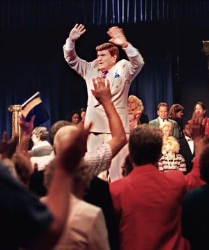 The Rev. Ernest Angley leads praise at a 1999 worship service at Grace Cathedral in Cuyahoga Falls.