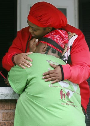Jhovonne Taylor (back to the camera) gets a hug from a neighbor the morning after her 14-year-old daughter, Ty'Leia Junius, was killed outside their Brighton Drive home. Ty'Leia and a 24-year-old man were both fatally injured, while another man was struck in the leg by a bullet but survived.