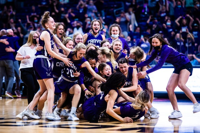 Canyon runs onto the court in dog pile fashion after making a comeback in the last minute to win the the 4A state final against Hardin-Jefferson at the Alamodome in San Antonio Thursday afternoon. [Matt Smith/for the Amarillo Globe-News]
