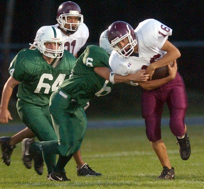 D-Y's Chris Marsh, left (64) adds defensive pressure to Falmouth's Lee Huffman in a  game in 2003. Marsh makes his debut as head coach for his alma mater Saturday against North Quincy.