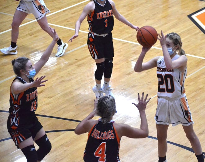 Cheboygan junior guard CJ Salter (20) shoots over Rudyard defenders Chesney Molina (left) and Laine Grenfell (4) during the first half of a varsity girls basketball matchup on Wednesday.