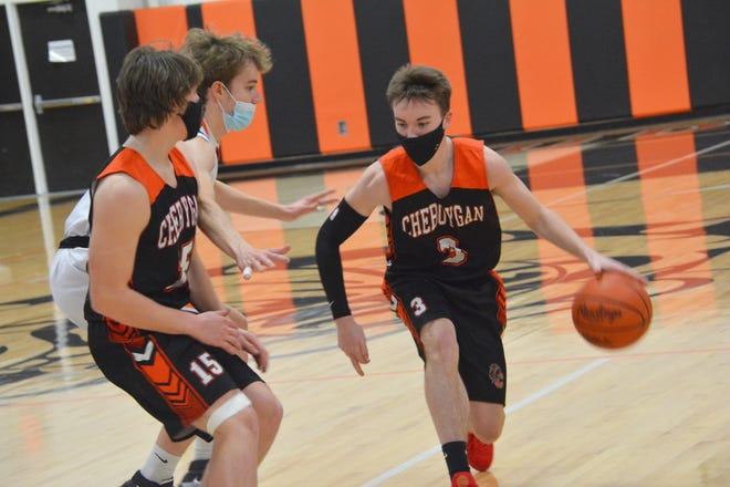 Carson Mercer (3) of Cheboygan dribbles around a pick from Henry Stempky (15), as Rudyard's Hayden Mills (3) tries to recover defensive position during Wednesday's game. The Bulldogs downed the Chiefs 49-31.